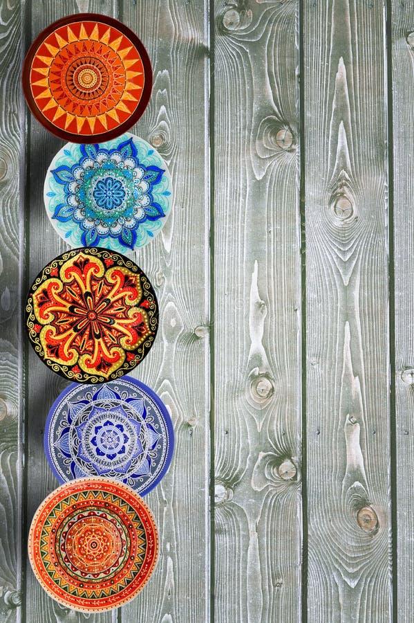 Pionowo set dekoracyjna ceramiczna talerz ręka malował kropka wzór z akrylowymi farbami na szarym drewnianym tle kosmos kopii fotografia royalty free