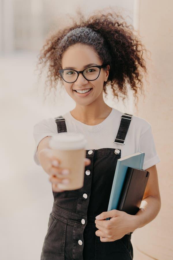 Pionowo strzał ładna kobieta z włosy curlly, chwyt takeaway kawa, napój podczas przerwy przy uniwersytetem, jest ubranym szkła, i zdjęcia stock