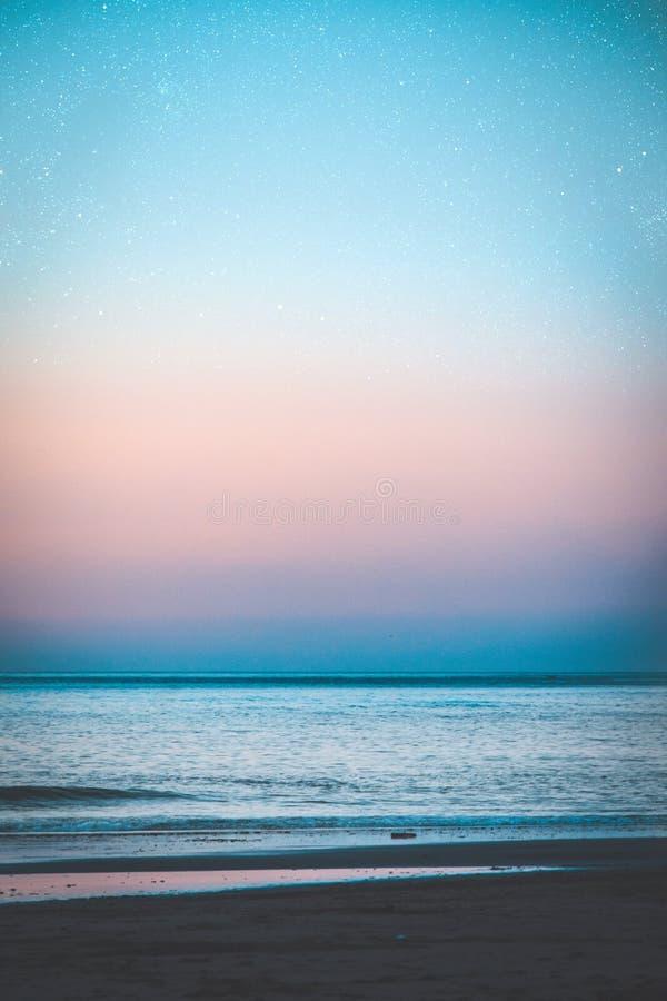 Pionowo strzał piękny wybrzeże morze z zadziwiającym purpurowym niebem pełno gwiazdy obraz royalty free