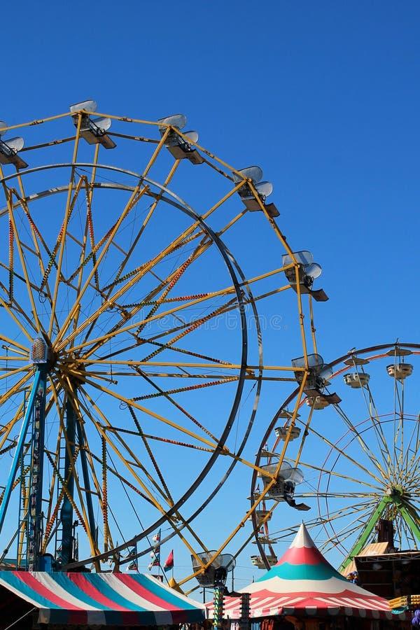 Pionowo widok dwa kolorowy Ferris toczy wewnątrz sylwetkę przeciw jaskrawemu błękitnemu lata niebu z namiotowymi pawilonami below zdjęcie royalty free