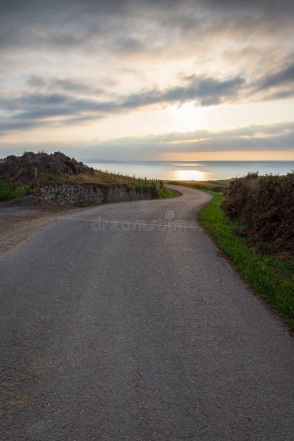 Pionowo widok osamotniona lokalna droga z zmierzchem na morzu obrazy stock