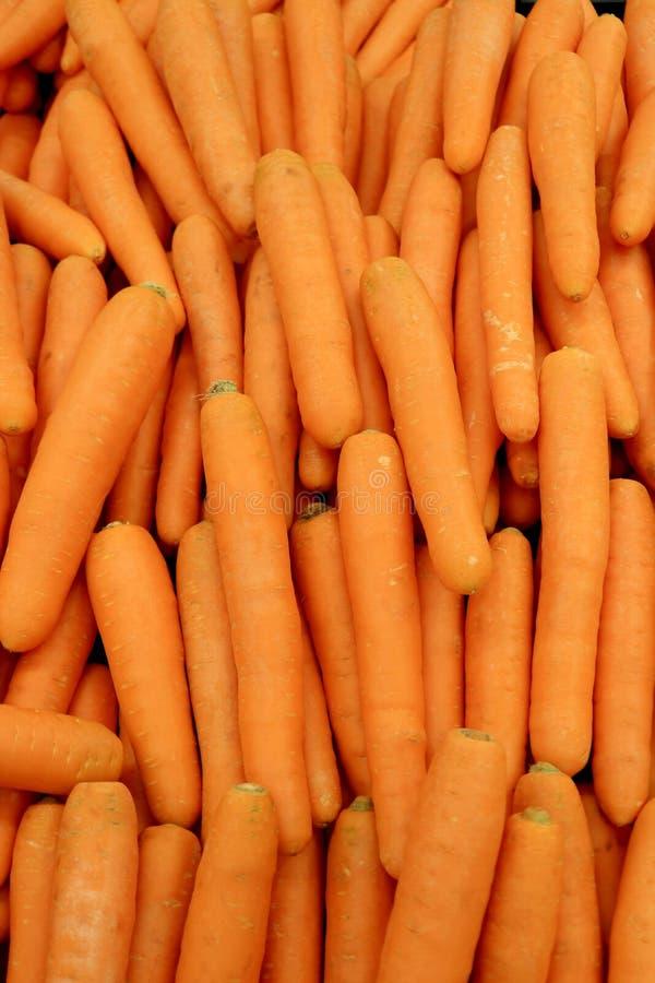 Pionowo wizerunek rozsypisko wibrującego pomarańczowego koloru świeże marchewki dla tła obraz stock