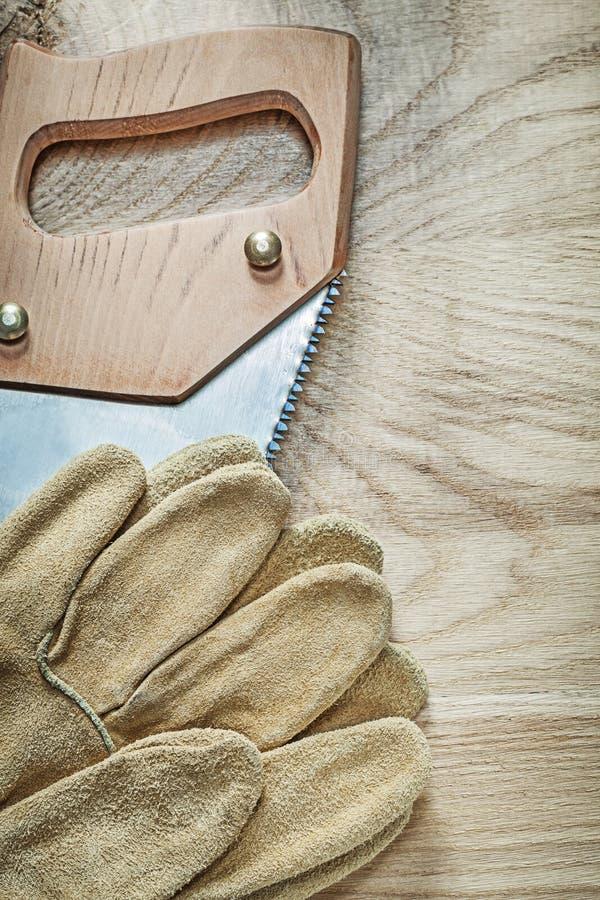 Pionowo wizerunek zbawczych rękawiczek nierdzewny hacksaw na drewnianym knurze zdjęcie stock