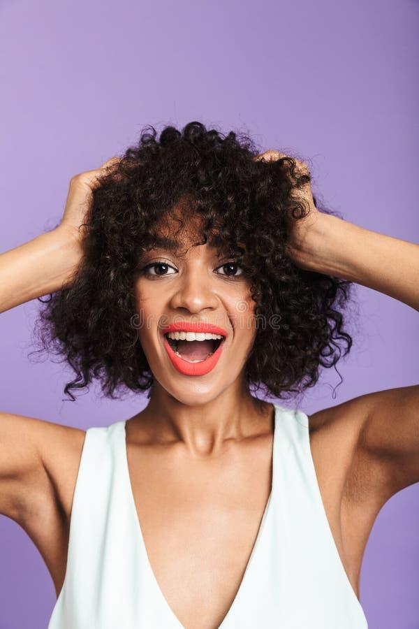 Pionowo wizerunek Zdziwiona szczęśliwa ładna afrykańska kobiety mienia głowa zdjęcia royalty free