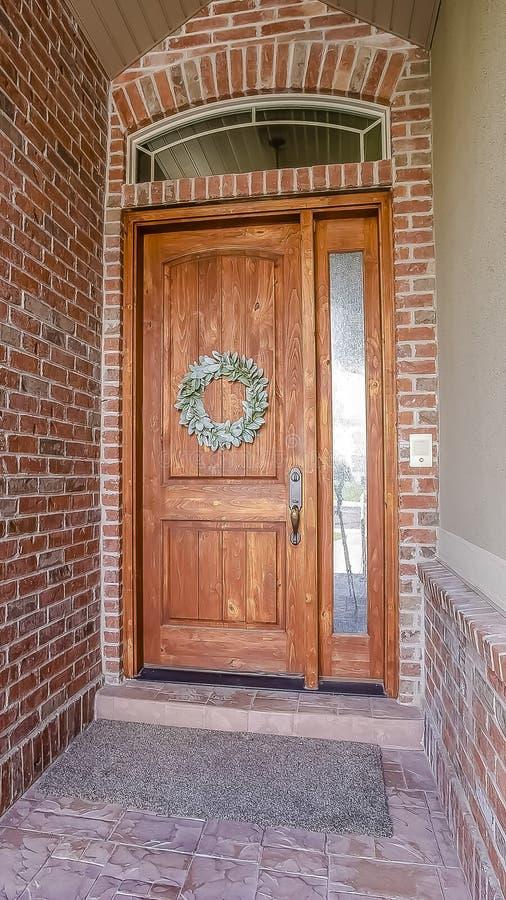 Pionowo wysoki ramowy Nieociosany drewniany drzwi z wianku sidelight i łukowatym transom okno zdjęcia stock