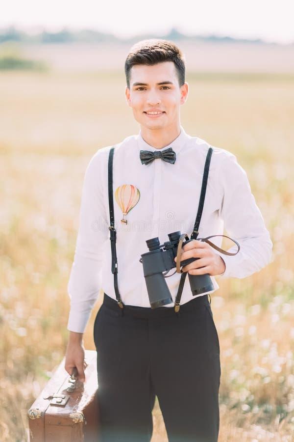 Pionowo zakończenie portret fornal trzyma i ono uśmiecha się przy kamerą rocznik walizkę i lornetki fotografia royalty free
