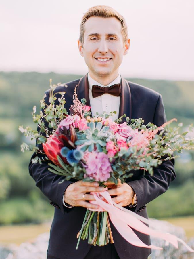 Pionowo zakończenie portret uśmiechnięty fornal trzyma ogromnego colourful ślubnego bukiet fotografia royalty free