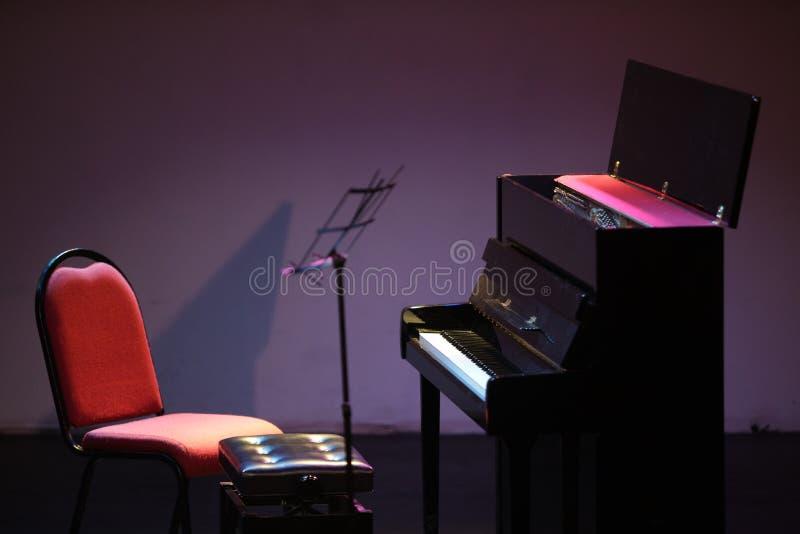 Pionowy pianino i muzyczny stojak na scenie, porzuconej zdjęcie stock