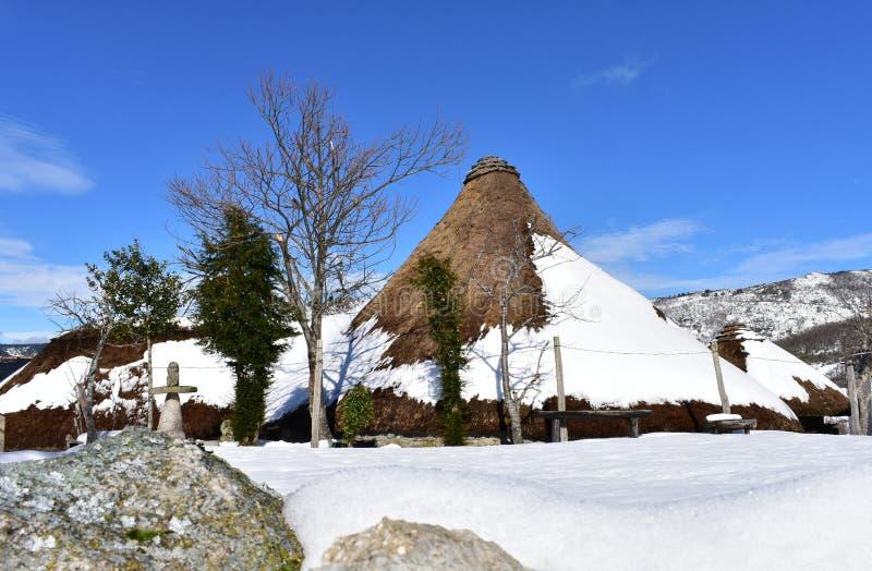 Piornedo,安卡雷斯山,加利西亚,西班牙 用石头和秸杆做的古老多雪的palloza房子 山村、冬天和雪 免版税库存照片