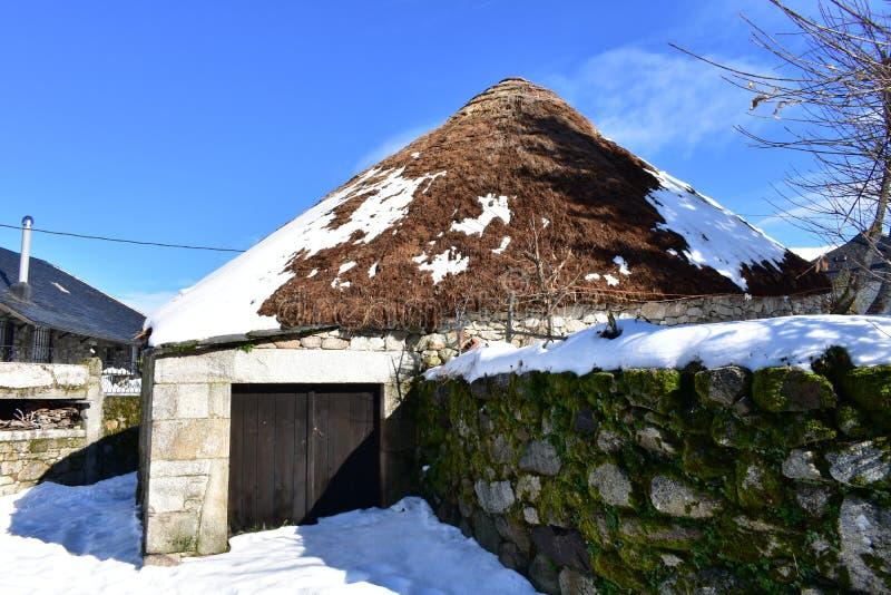 Piornedo Ancares, Galicia, Spanien Forntida snöig pallozahus som göras med stenen och sugrör Bergby, vinter och snö arkivfoton