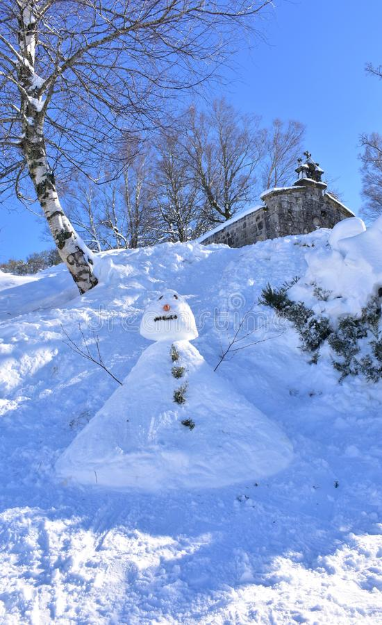 Piornedo, Lugo, Spain. San Lorenzo Hermitage covered with snow and snowman. Trees and blue sky, sunny day. stock photos