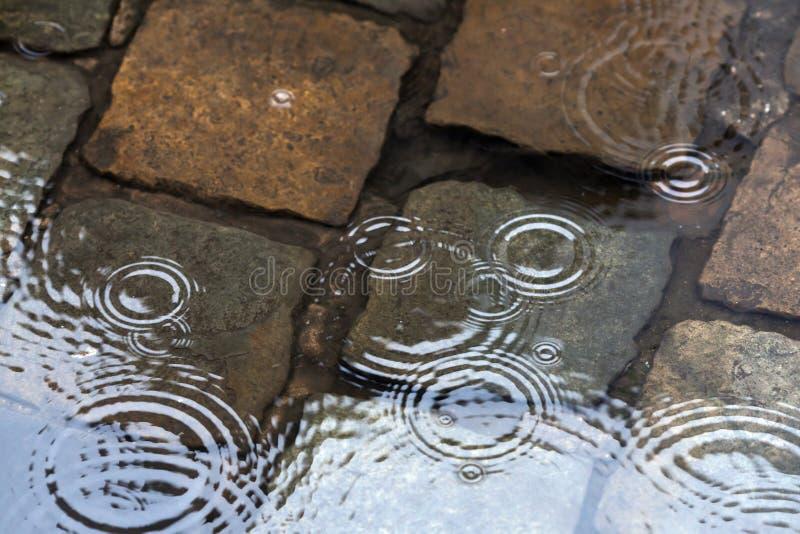 Piovendo sulla pavimentazione del cobblestone fotografia stock libera da diritti