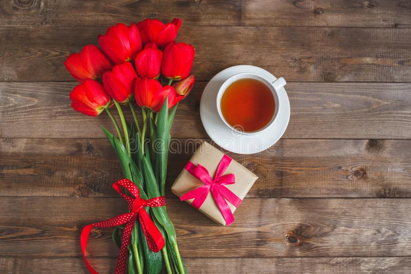 Piovuto appena sopra Mazzo dei tulipani rossi con la tazza di tè e la scatola attuale su fondo di legno marrone Festa della Mamma immagine stock libera da diritti