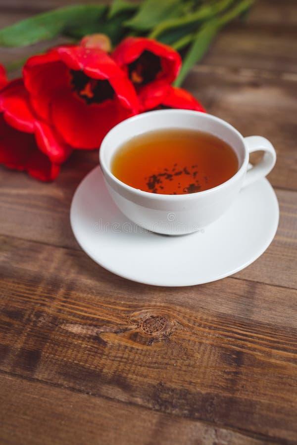 Piovuto appena sopra Mazzo dei tulipani rossi con la tazza di tè su fondo di legno marrone Concetto di giorno di biglietti di S.  fotografie stock