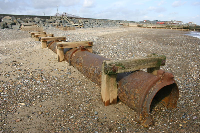 Rusty drain pipe on the beach. Rusty old pipe on a sand and shingle beach by the sea with promenade and resort in the distance on the east coast of Yorkshire stock photography