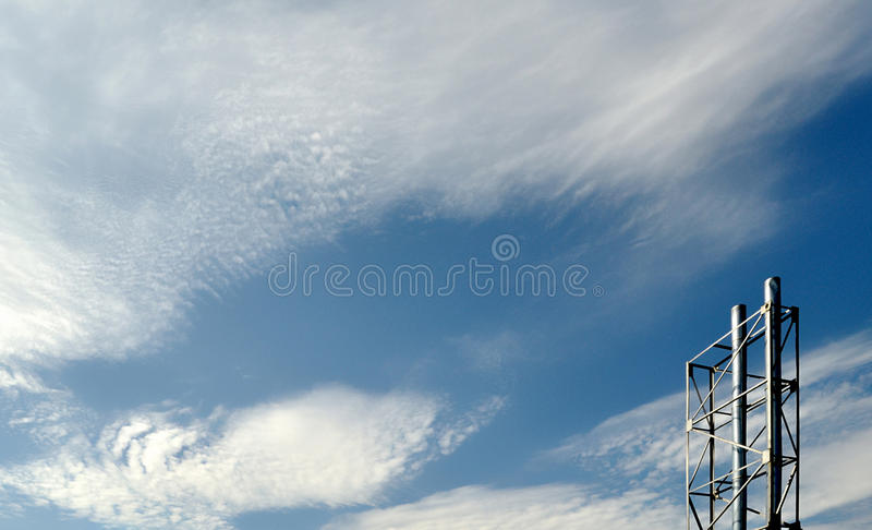Pipe de deux usines avec le ciel nuageux bleu image stock