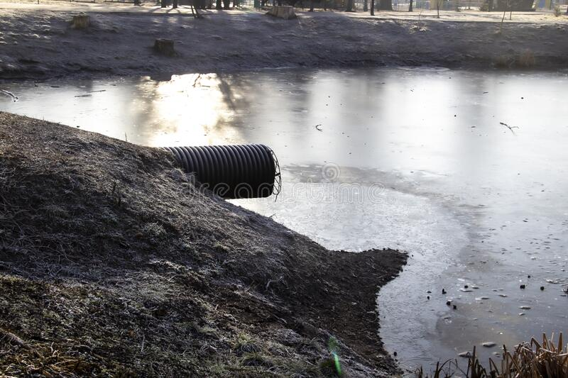 Pipe for draining sewage into a frozen lake in a park. Waste Discharge to the lake royalty free stock photos