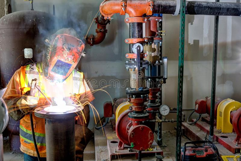 An industrial Pipe fitter welding a pipe connection. stock photo