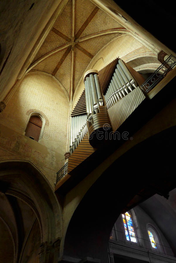 Pipe organ in Ancient French cathedral. A photograph showing the beautiful domed ceiling and antique pipe organs inside the ancient medieval Cathédrale Saint royalty free stock photos
