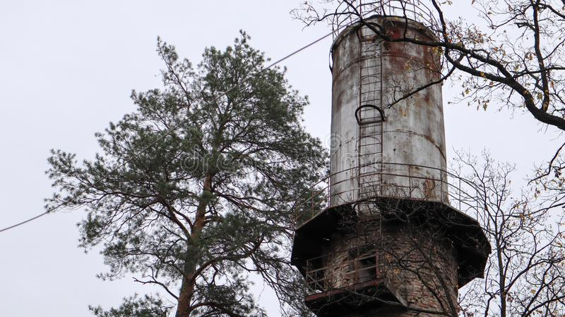 The pipe of the plant rise above the forest. Industrial landscape. Ecological production without smoke from pipes. Water tower in. The village. Water supply to royalty free stock photography