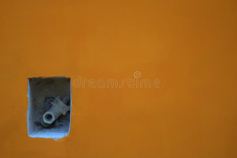 Pipe protruding from the orange yellow wall stock photography