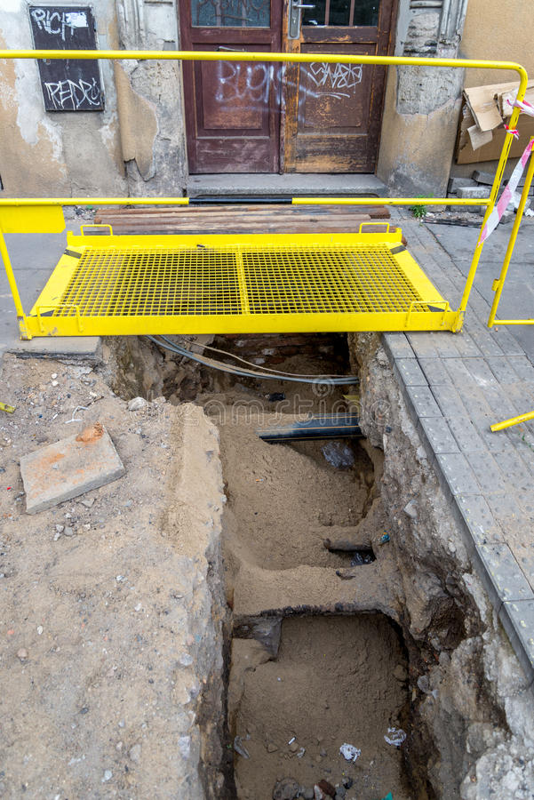 Pipe repair in footpath. With a yellow footbridge over the trench stock image