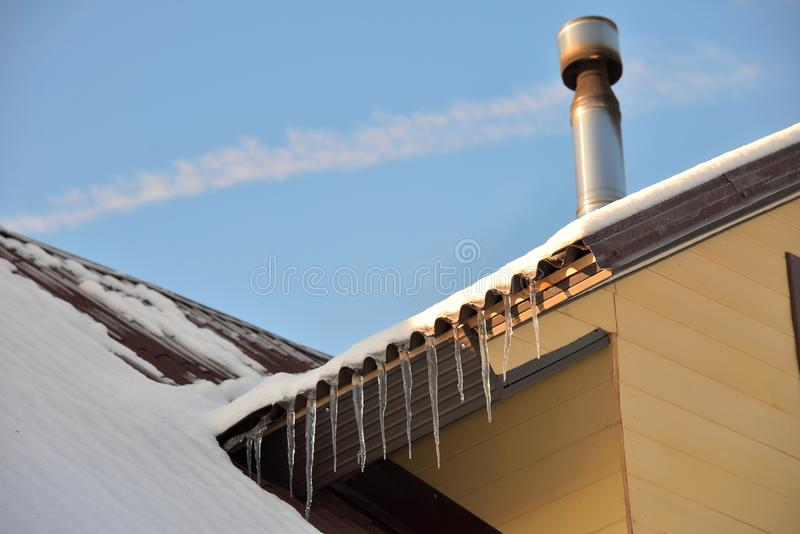 Pipe on the snow-covered roof with icicles of wooden house stock image