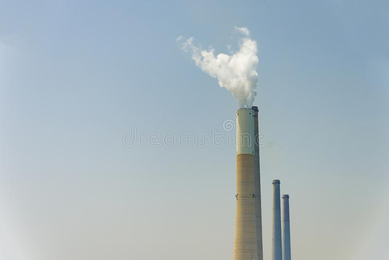 The pipe from which the smoke goes against the gray sky. The concept of air pollution stock image