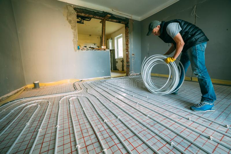 Pipefitter installing system of heating royalty free stock photos