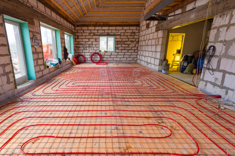 Pipefitter installing system of heating or underfloor heating installation. Water floor heating system interior. stock photo