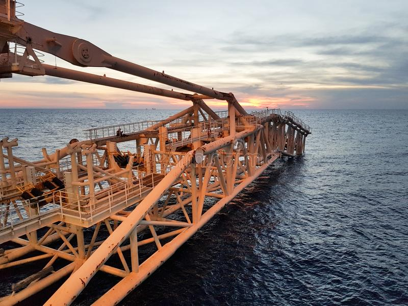 Pipelay Mode ON. A pipeline stinger of a pipelay barge above sea surface during sunset stock images