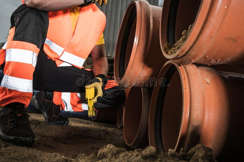 Pipeline Construction Project. Sewage Pipeline Construction Project. Worker Preparing Plastic Pipes For Installation. Industrial Theme royalty free stock image