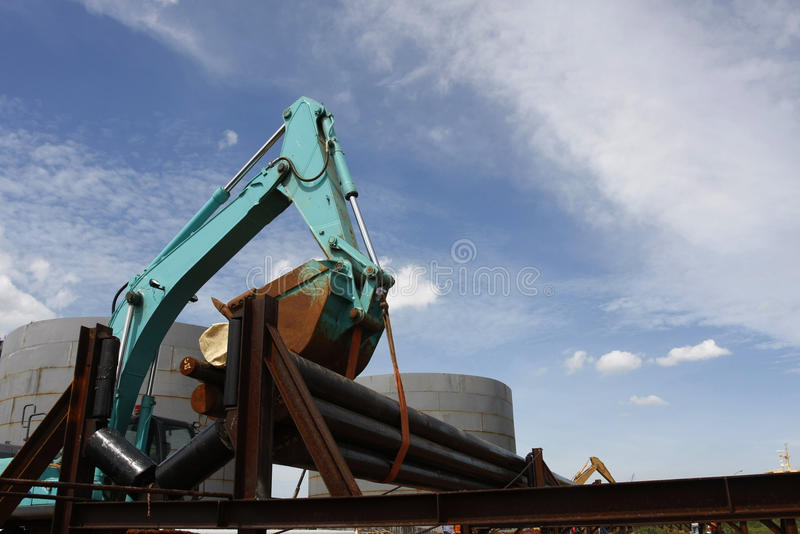 Pipeline Project. Escavator lift pipes to the rail at gas pipeline project royalty free stock image