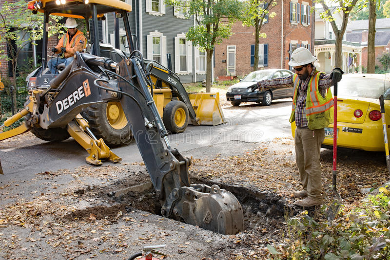 Pipeline Worker Directing Backhoe. Dayton, Ohio, USA - October 25, 2016: Miller Pipeline workers dig up residential street in St. Anne's Hill Historic District royalty free stock image