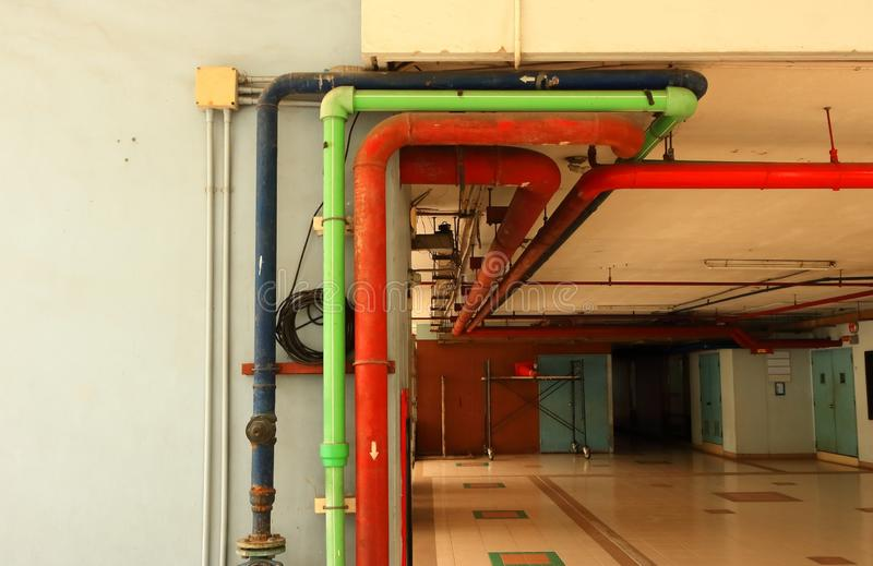 Pipelines. Closeup of pipes and electrical junction box fixed to the wall and ceiling of a building stock images
