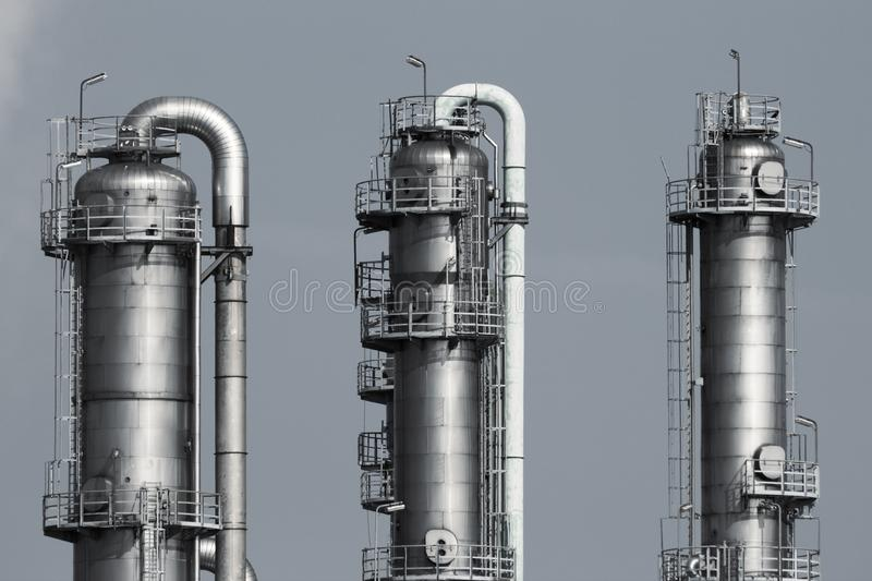 Pipelines of a oil and gas refinery industrial plant. Cooling towers at an oil and gas refinery industrial plant stock image