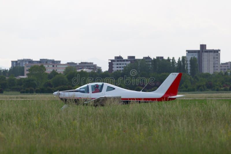 Piper Aircraft Taking branca pequena e clara fora da pista de decolagem entre o prado fotos de stock royalty free