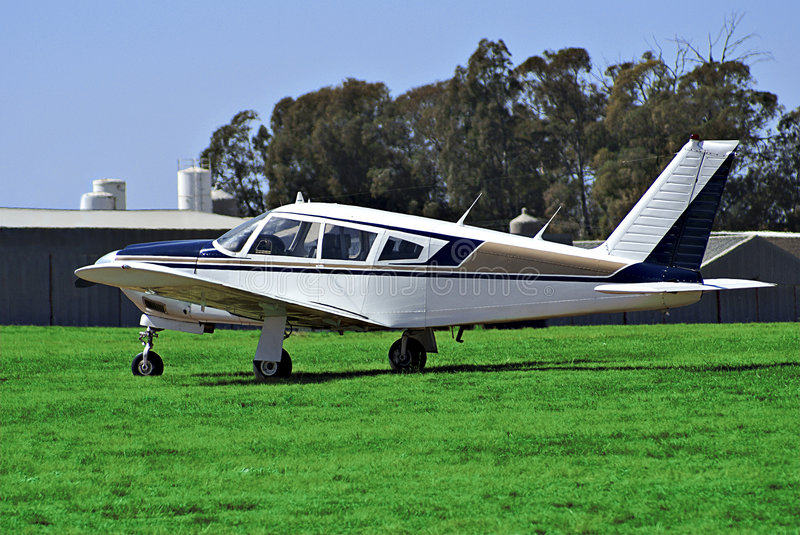 Piper Arrow 200 - Summer. This light aircraft [Piper Arrow 200] is parked down at the back of the airport, in front of some of the hangars, seen in the royalty free stock image