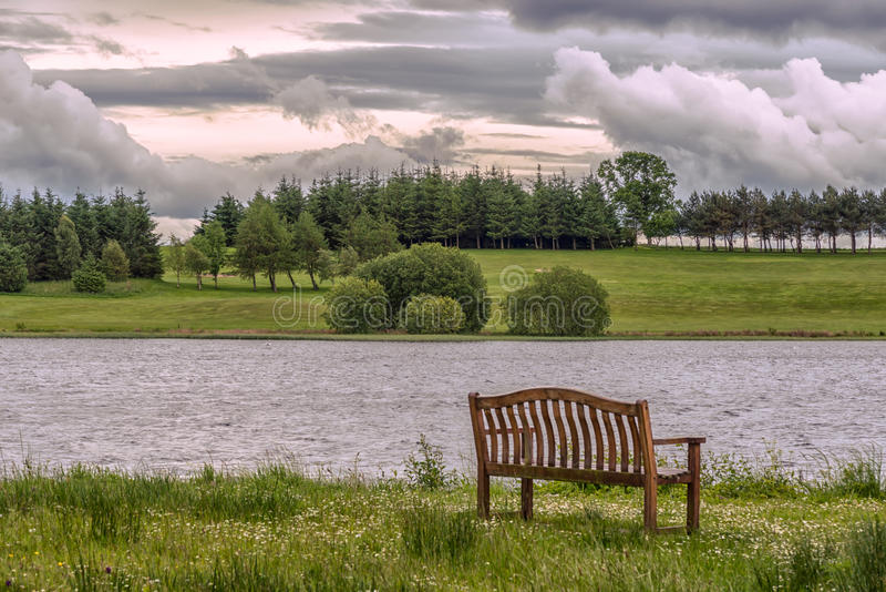 Piperdam Lake and an isolated chair in Scotland royalty free stock photography