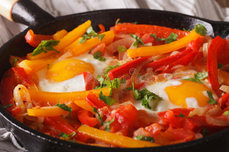 Piperrada: peppers with fried eggs on the pan macro. horizontal. Piperrada: peppers with fried eggs on the frying pan macro. horizontal stock photos