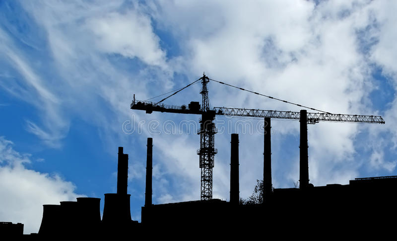 Pipes of coal burning power station and construction crane stock image