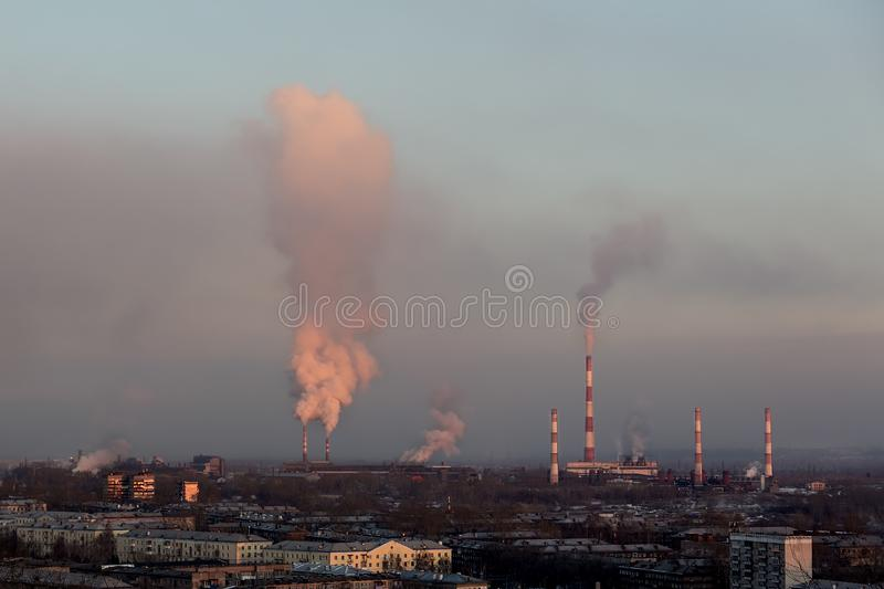 The pipes of the factories smoke in the rays of the setting sun, and multi-storey houses stand before them.  stock image