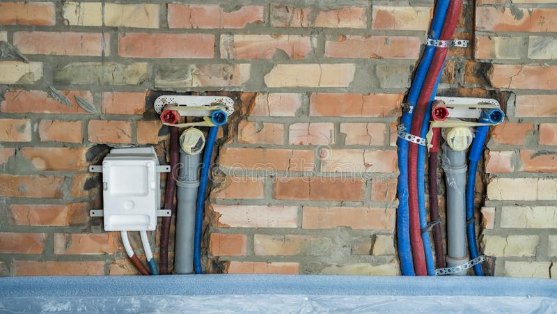 Pipes for hot and cold water and sewage pipes mounted in the wall royalty free stock image