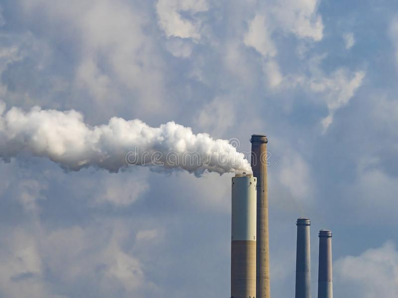 Pipes of a large enterprise against the cloudy sky. White smoke comes out of one pipe. royalty free stock photos