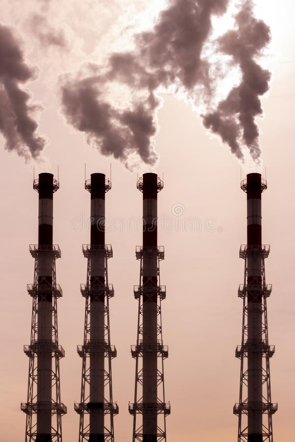 A group of pipes releases dark smoke steam vapor. environmental pollution, air pollution by toxic fumes stock images