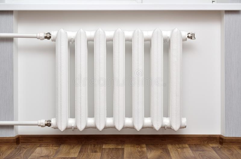 Pipes and a white heating radiator heat the room.  royalty free stock photo