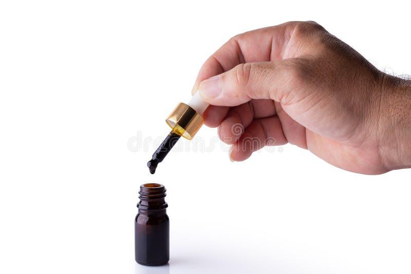 Pipeta de la tenencia de la mano del aceite del cáñamo sobre una botella imagenes de archivo