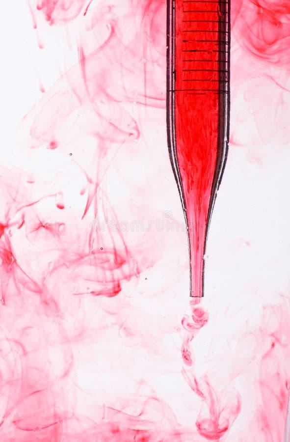 Pipetta con liquido rosso immagini stock