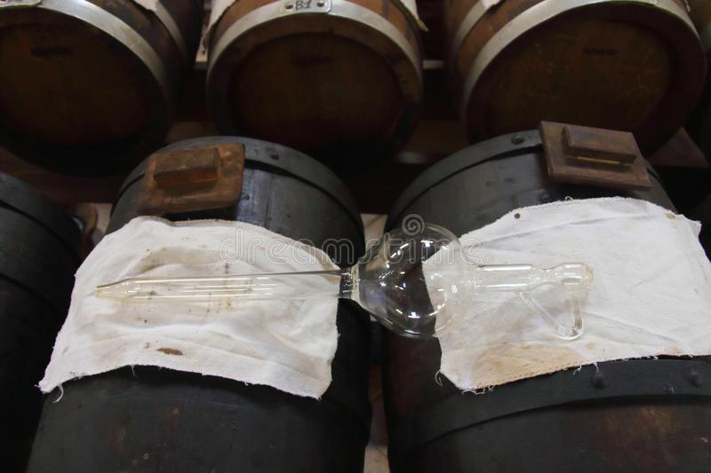 Pipette for Balsamic Vinegar of Modena. Pipette for suction posed on a `Batteria` that is a series of barrels of different kind of woods for the production of stock photos