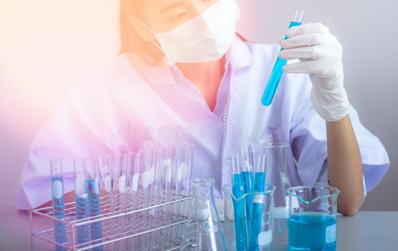 Young Asian scientist with test tube making research in clinical laboratory.Science, chemistry, technology, biology and people con. Pipette dropping a sample in stock images